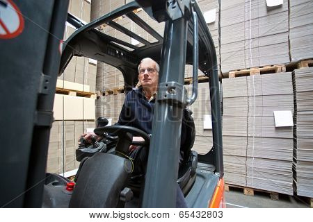 Forklift driver inside a forklift, manipulating a joystick in a warehouse full of pallets empty, plano, cardboard boxes