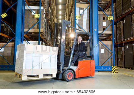 Forklift driver posing in front of a row with storage racks. On his fork he is transporting a pallet full of flat cardboard boxes.