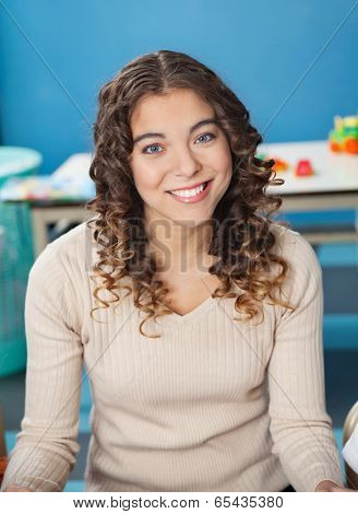 Portrait of beautiful young teacher with smiling in kindergarten