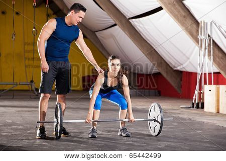 Cute young brunette getting some tips on her workout from her personal trainer at a gym poster