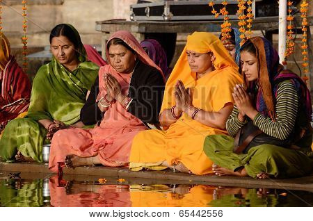 senior women perform puja - ritual ceremony at holy Pushkar town,India
