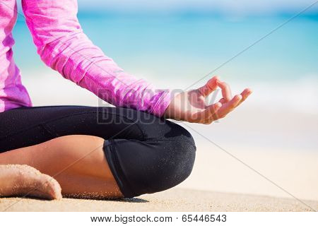 Happy relaxed young woman practicing yoga outdoors at the beach. Lotus position, Cloe up detail photo of hand.