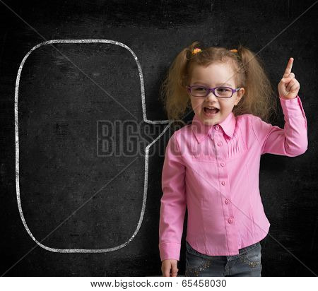 Funny child in eyeglasses standing near school chalkboard  as a teacher with blank speech bubble sketch.