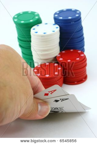 Poke player views pocket pair of aces, stack of chips
