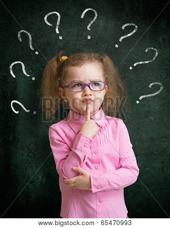 Child in eyeglasses standing near school blackboard with many question marks