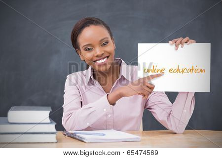 Happy teacher holding page showing online education in her classroom at school