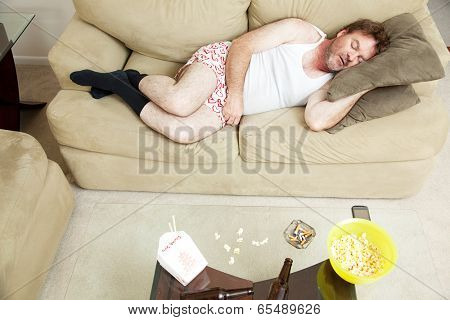 Overhead view of an unemployed man sleeping on the couch in his underwear, with food, beer, and cigarettes on the coffee table.