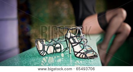 Close-up of female high heels black sandals and young woman legs with black long stockings