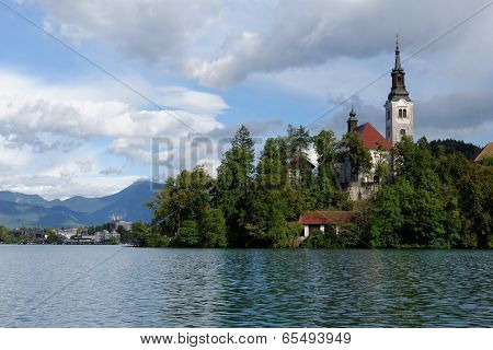 Church on an island on Bled lake with mountains and resort on the background