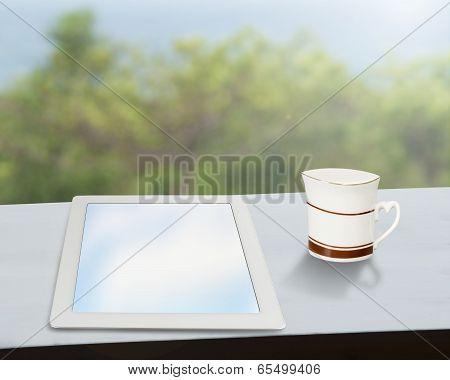 Tablet With Coffee Mug On Window Side Table
