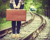 young woman with old suitcase on railway departing train on background retro stylized poster