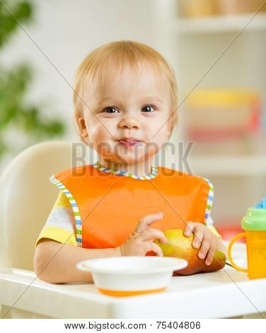 happy baby kid boy toddler eating itself with spoon