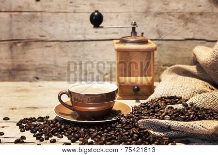Coffee Cup, Beans And Grinder In Front Of Vintaged Wooden Background