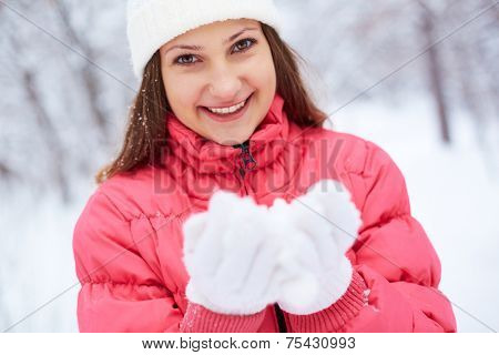 Portrait of pretty girl in winterwear holding snow on palms
