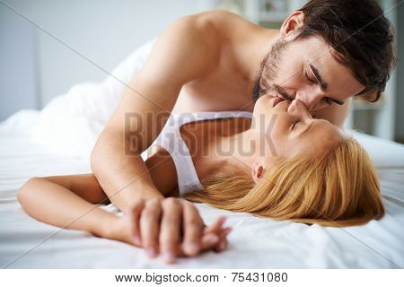 Amorous couple cuddling in bed poster
