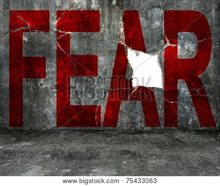 Red Fear Word On Mottled Concrete Wall With Large Hole