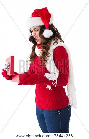Disgusted brunette opening christmas gift on white background