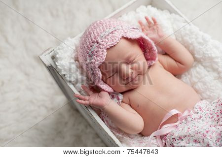 Smiling Newborn Baby Girl Wearing A Pink Bonnet