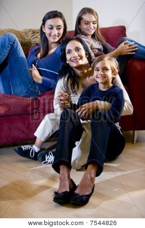 Mother With Three Children Relaxing On Living Room Sofa