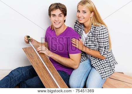 Young couple measuring woodblock