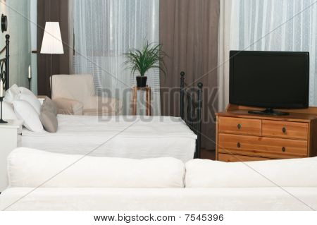 The Big Tv In A Room Before A White Sofa. A Bedroom With A Bed