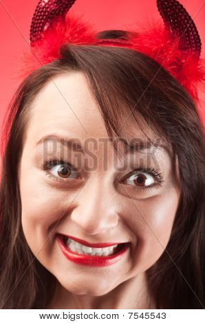 Facial Portrait Of A Beautiful Young Woman In Devils Horns On Red Background. Close Up