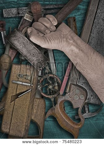 faded colors of a vintage woodworking tools and hand holding hammer on wooden bench