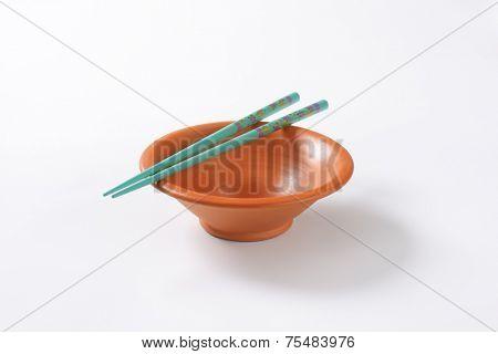 pair of blue chopsticks and empty orange bowl on white background