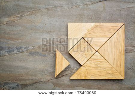 a missing piece in a square built from tangram pieces, a traditional Chinese puzzle game, slate rock background