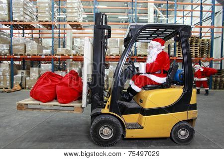 Rush hours before Christmas.Santa Claus as a forklift operator at work in warehouse