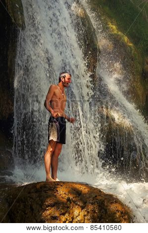 young man shrieking with joy standing on rock beside a beautiful waterfall