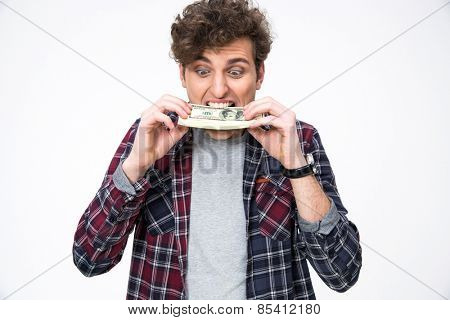 Young casual man biting money over gray background