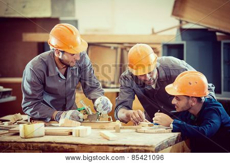 Team working on project in industrial wood factory
