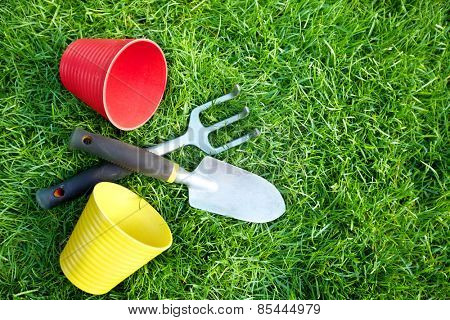 Gardening tools on green grass in the garden.