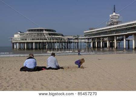 People Sitting In The Spring Sun Before The Pier Of Scheveningen
