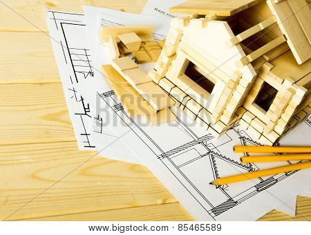 Many drawings for building, pencils and small house on wooden background.