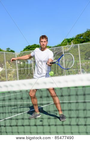 Tennis. Tennis player hitting ball in volley by the net. Male athlete playing outdoors on hard court practicing in summer. Young Caucasian man living healthy active fitness sport lifestyle outside.