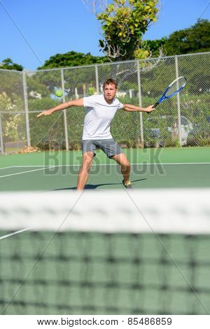 Tennis player - man hitting forehand playing outside on hard court. Male sport fitness athlete practicing in summer outdoors living healthy active lifestyle.