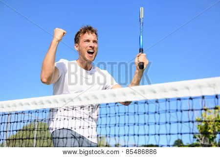 Tennis player celebrating victory. Winning cheering man happy in celebration of success and win. Fit male athlete winner on tennis court outdoors holding tennis racket in triumph by the net. poster