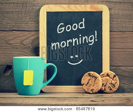 Cup Of Tea With Cookies And Blackboard With Phrase Good Morning!