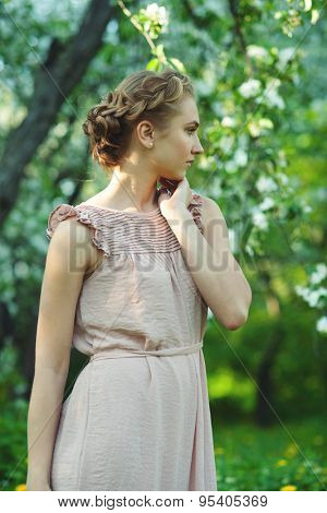 Portrait of girl with beautiful updo hairstyle with tress in summer garden, summertime