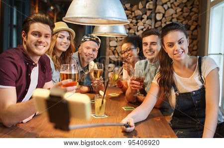 people, leisure, friendship, technology and party concept - group of happy smiling friends with smartphone on selfie stick and drinks taking picture at bar or pub