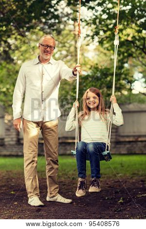 family, happiness, generation, home and people concept - happy grandfather and  granddaughter swinging on teeterboard outdoors
