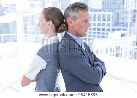 Two angry business colleagues standing back to back in the office