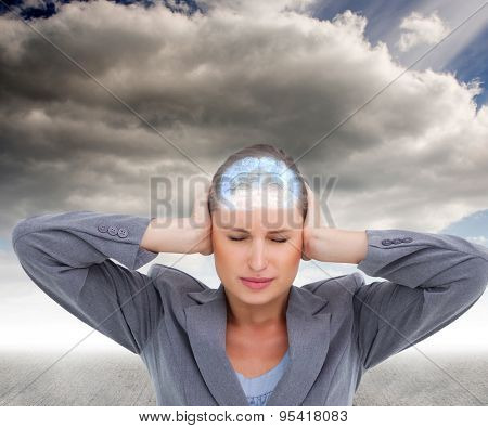 Close up of annoyed tradeswoman covering her ears against cloudy sky