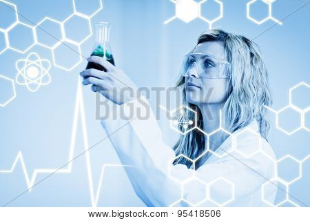 Science graphic against woman in lapcoat looking at chemicals