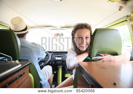 Cheerful couple riding camper van