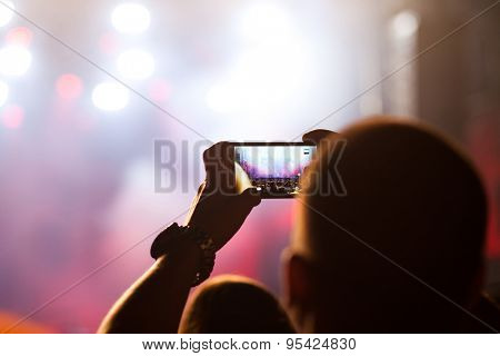 BONTIDA, ROMANIA - JUNE 27, 2015: Crowd of partying people taking photos with smartphone at Electric Castle festival, one of the biggest music festivals in Romania.