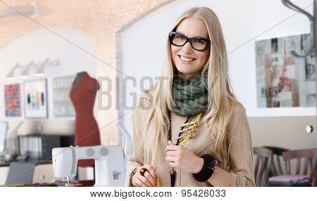 Portrait of happy casual trendy caucasian blonde fashion designer businesswoman at studio. Smiling, standing, looking at camera. poster