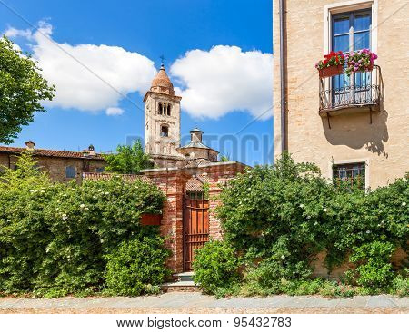 Brick fence covered with green bushes and parish church on background in small town in Piedmont, Northern Italy.
